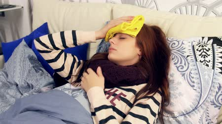 doente : A sick woman sleeping with wet towel on his forehead to reduce high high fever