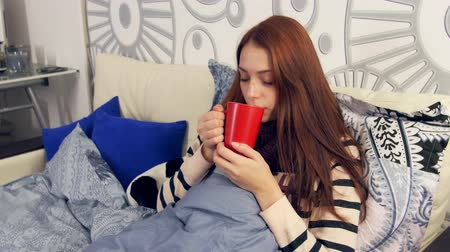 cold : Young woman suffering from cold, flu symptoms, drinking a hot beverage while wrapped in a warm blanket.