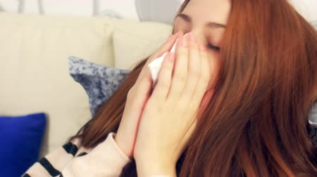 грипп : Sick woman in bed coughing and blowing nose in paper tissue