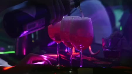 boate : Mans hand pours champagne in glasses with cocktail in nightclub. Slow motion