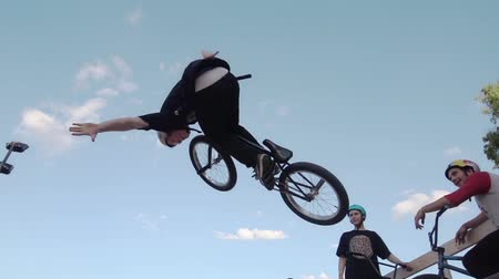 převrátit : Boy make extreme jump on BMX bicycle in skate park, let go steering wheel in air.