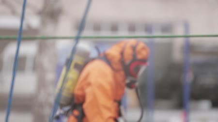apocalyptic : Men in orange protect suits, respiratory masks save man. Chemical disaster
