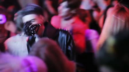 itaatkâr : Sexy man in collar, jaket and muzzle with spikes dance in crowded nightclub.