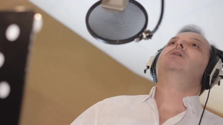 waggle : Portrait of man sing in headphones in front of microphone. Studio. Waggle Stock Footage