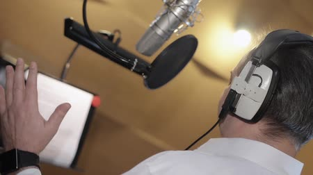 caz : Back side of man emotionally sing in headphones in front of microphone. Studio Stok Video