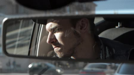 okulary przeciwsłoneczne : Mirror of car focus in. Driver look in mirror and put on sunglasses. Traffic jam