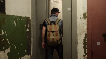 entry level : Man in cap with backpack walk in old elevator. Choose floor. Ragged walls