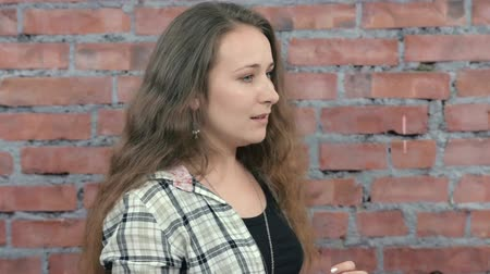 excuses : Young girl offer excuses someone behind the scene. Casting. Brick wall background. Emotions Stock Footage