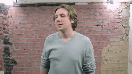 excuses : Adult man offer excuses and speak on camera. Brick wall background. Audition. Casting