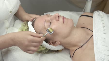 лечение : Cosmetologist make galvanotherapy face of adult woman in beauty saloon. Skincare. Close up