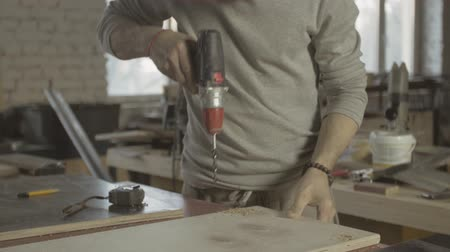 perforation : Professional aged carpenter perforate holes in polished wooden board by drill. Manufactoring Stock Footage