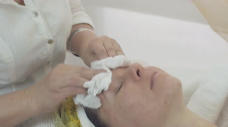 wipe off : Close up of cosmetologist wipe off woman face by napkin after mask in beauty saloon. Skincare. Cosmetic procedure.