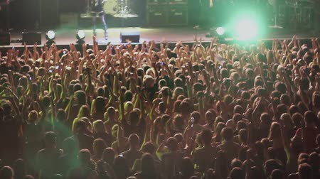 rock concert : View of crowd people raise hands on rock concert in nightclub. Band performing on stage. Spotlights