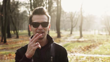 koppintás : Portrait of young man in sunglasses hold both hands together in camera and walk away. Autumn park. Sunny day. Rap artist
