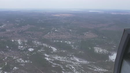 pilot in command : Aerial view from helicopter. Camera inside. Landscape of field with green forest, some snow. Transportation. Height