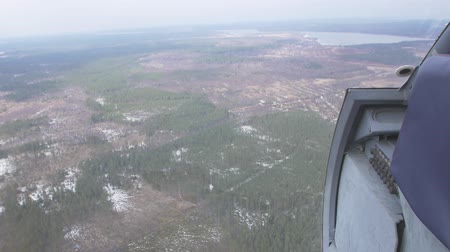 pilot in command : Aerial view from flying helicopter. Camera inside. Landscape of green forest, some snow. Transportation. Height