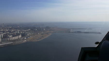 pilot in command : Aerial view from helicopter fly above water. Height. City at coast. Seaport. Sunny day. Transportation.