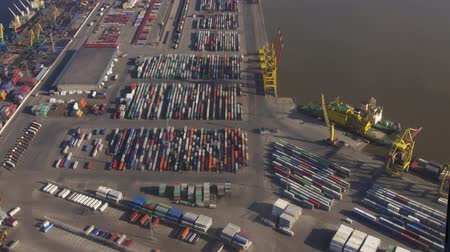 pilot in command : Aerial view from helicopter fly above colorful cargo containers in seaport. Height. Sunny day. Transportation. Stock Footage