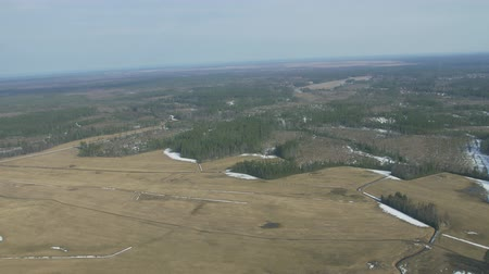 pilot in command : Aerial view from helicopter fly above green forest, field. Camera inside. Height. Some snow. Landscape. Transportation. Stock Footage