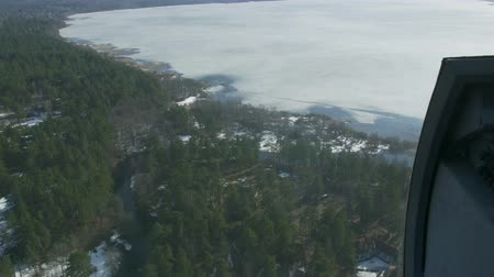 pilot in command : Aerial view from helicopter fly above green forest and frozen lake. Camera inside. Landscape. Ice. Transportation.