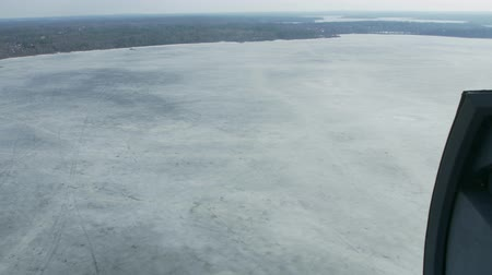 pilot in command : Aerial view from helicopter fly above frozen lake at green forest. Camera inside. Landscape. Ice. Transportation. Stock Footage