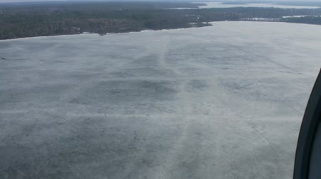 pilot in command : Aerial view from helicopter fly above frozen lake at green forest. Camera inside. Ice water surface. Transportation. Stock Footage
