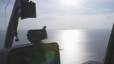 pilot in command : Cabin of pilot helicopter aerial view above sea. Height. Sunbeams on water surface. Sunny day. Transportation. Stock Footage