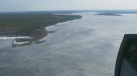 pilot in command : Aerial view from helicopter fly above frozen lake at green forest. Camera inside. Height. Ice. Transportation.