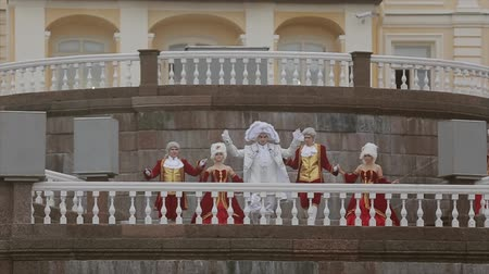 haughty : Men and lady in historical old royal dresses, in white periwigs walk on marble plinth. Event. Slow motion