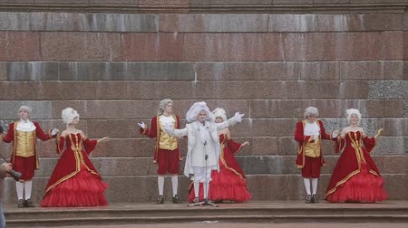 haughty : Men and lady in historical old royal dresses, in white periwigs perform on marble plinth. Event. Cameraman. Slow motion Stock Footage