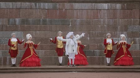 haughty : Men and lady in historical old royal dresses, in white periwigs perform on marble plinth. Event. Applause. Slow motion