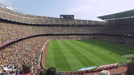 estádio : Football stadium in Spain. Crowds of fans on tribunes. Footballers play on field. Summer sunny day. Emotions. Slow motion