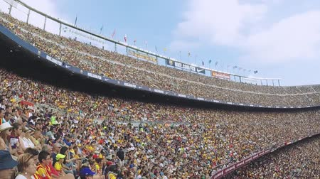 fan zone : Football stadium in Spain. Crowds support players on tribunes. Teams on field. Summer sunny day. Slow motion Stock Footage
