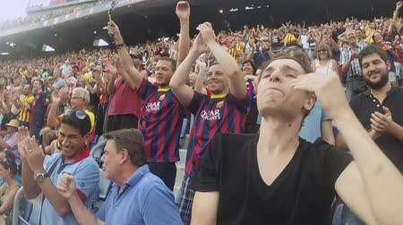 fan zone : Football stadium in Spain. Fans support players on tribunes. Raise hands. Emotions. Whistling. Summer day. Slow motion Stock Footage