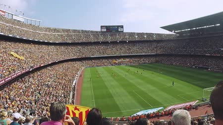 fan zone : Football stadium in Spain. Fans support players on tribunes. Teams on field. Summer sunny day.  Slow motion
