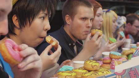 doughnut : People eat doughnuts covered by glaze at table on speed. Challenge. Championship. Shopping center.