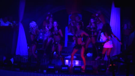 discotheque : Sexy go go girls in black bikini synchronously dance on stage of nightclub. Ultraviolet
