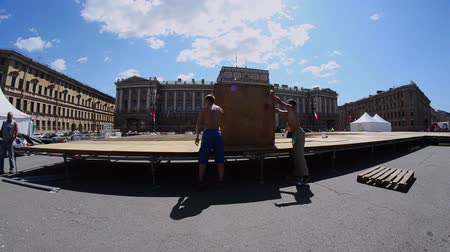 eljárás : Workers build street stage for summer event. Construction. Wooden boards. Sunny day.