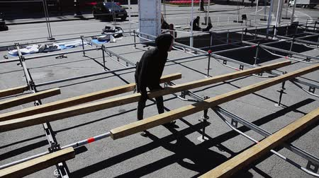eljárás : Workers build street stage for event. Construction. Man lay out wooden boards. Sunny day