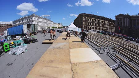 eljárás : Workers building street stage for summer event. Lay out wooden boards on balks. Sunny day. Stock mozgókép