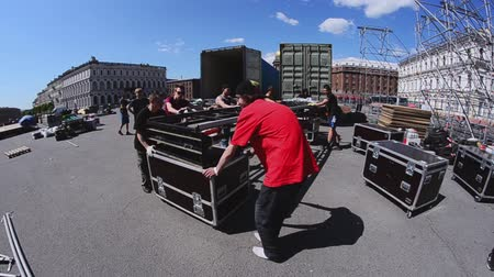 eljárás : Workers build street stage for summer event. Moving construction stairs to truck. Sunny day. Stock mozgókép