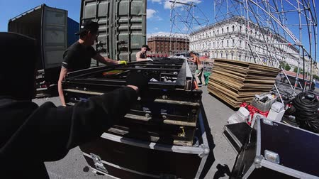 eljárás : Workers build street stage for summer event. Moving construction stairs to stage. Sunny day.