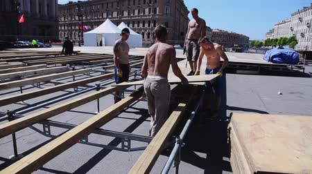 eljárás : Workers building stage for event on street. Lay wooden boards on balks. Sunny day.
