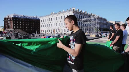 eljárás : Workers building street for summer event on street. Men hold green huge tent. Saint Petersburg