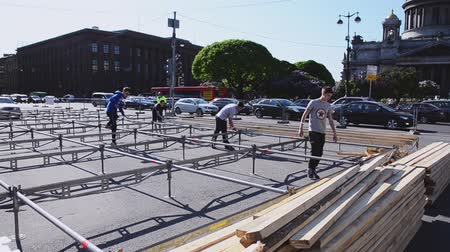 eljárás : Young boys building stage for event on street. Lay out wooden boards. Workers. Saint Petersburg