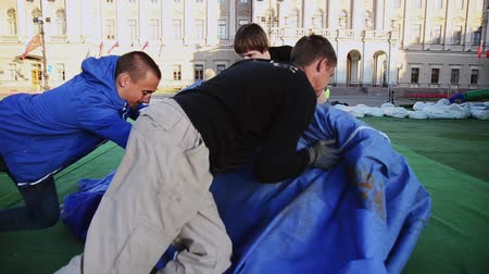 eljárás : Men move blue bag with green tent. Workers building stage for event on street. Sunny day. Stock mozgókép
