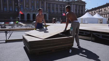 eljárás : Men building stage for summer event on street. Workers carry wooden boards. Sunny day.