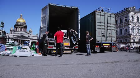 eljárás : Men building stage for event on street. Workers carry equipment from truck. Sunny day.