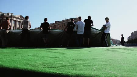 eljárás : Men building stage for event on street. Workers carry huge tent. Green carpet. Sunny day.