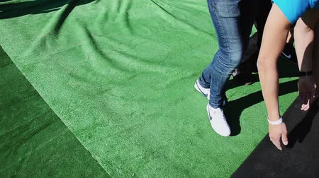 eljárás : Young men lay out huge green carpet. Build stage for event on street. Workers. Sunny day. Stock mozgókép